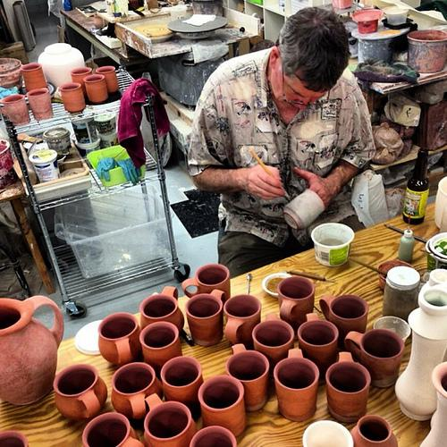 A potter in Seagrove glazes cups.