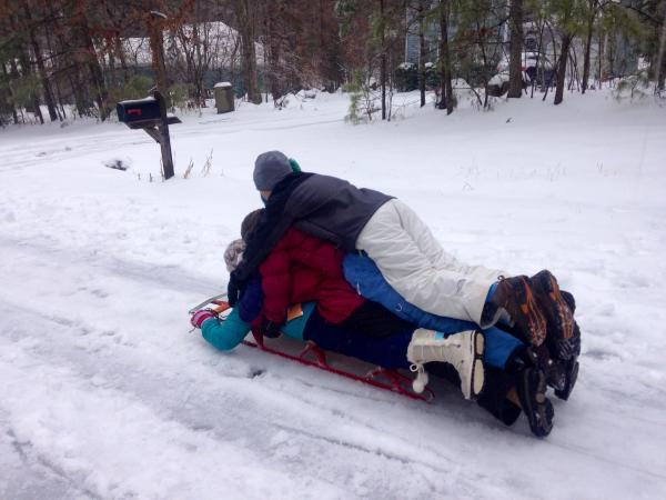 16 year old Bailey Revels from Chatham County (in blue pants) piles on a sled with her younger brother and two neighbors.