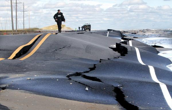 A Dare County sheriff's deputy walks down damaged Route 12 after Hurricane Sandy in October 2012.