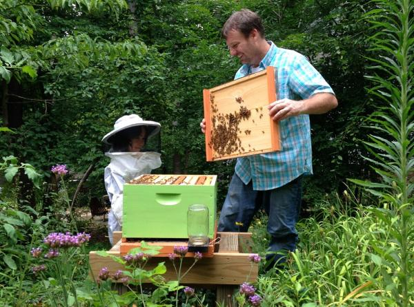 Marty Hanks teaches a child about the bees in her grandmother's front yard.