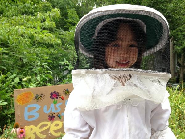 This little girl is posing at her grandmother's home in Chapel Hill. She made the sign behind her to welcome the bees.