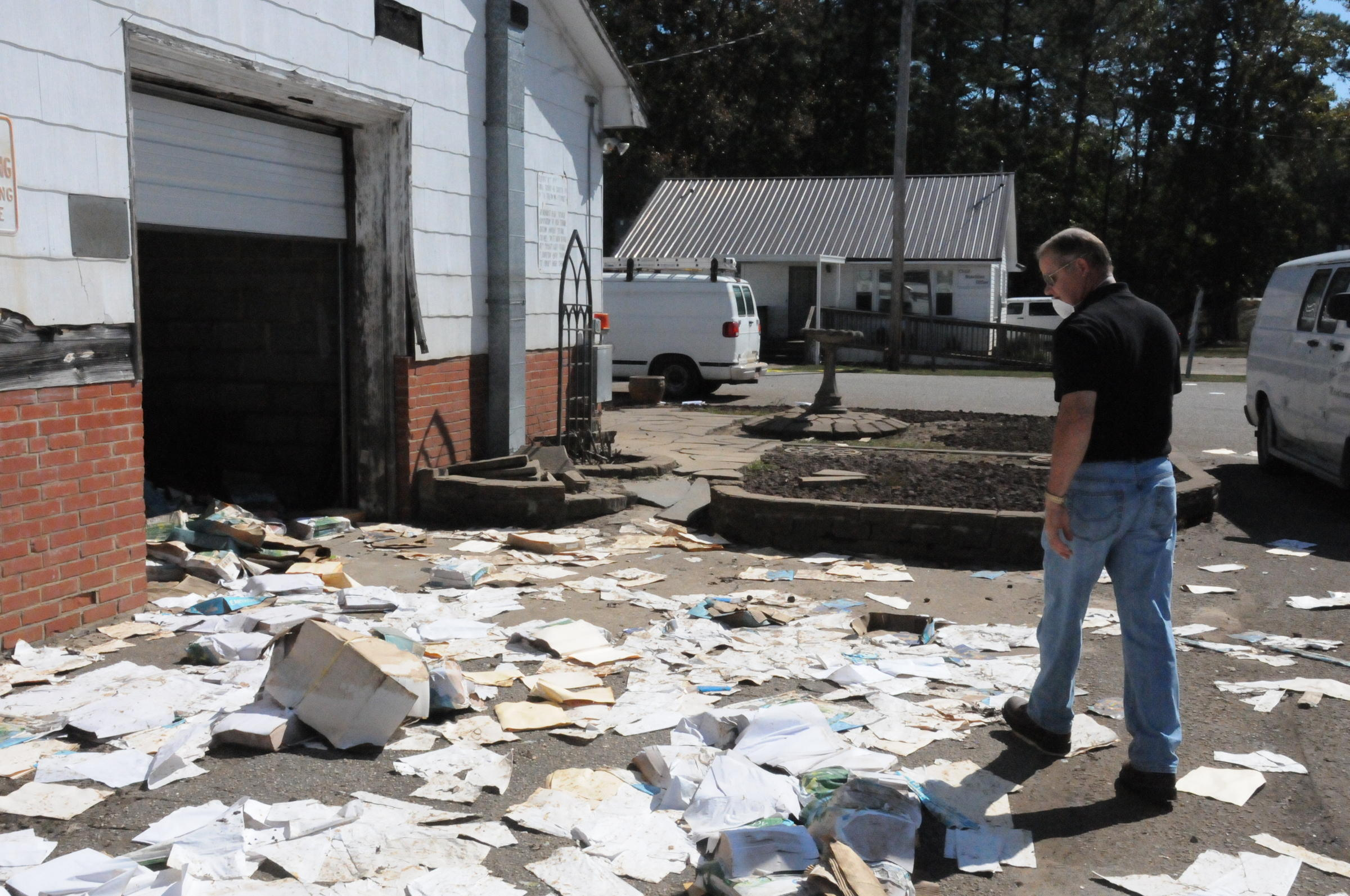 Robeson Schools Superintendent Tommy Lowry surveys the damage outside the  textbook and supply warehouse at the district's central services.