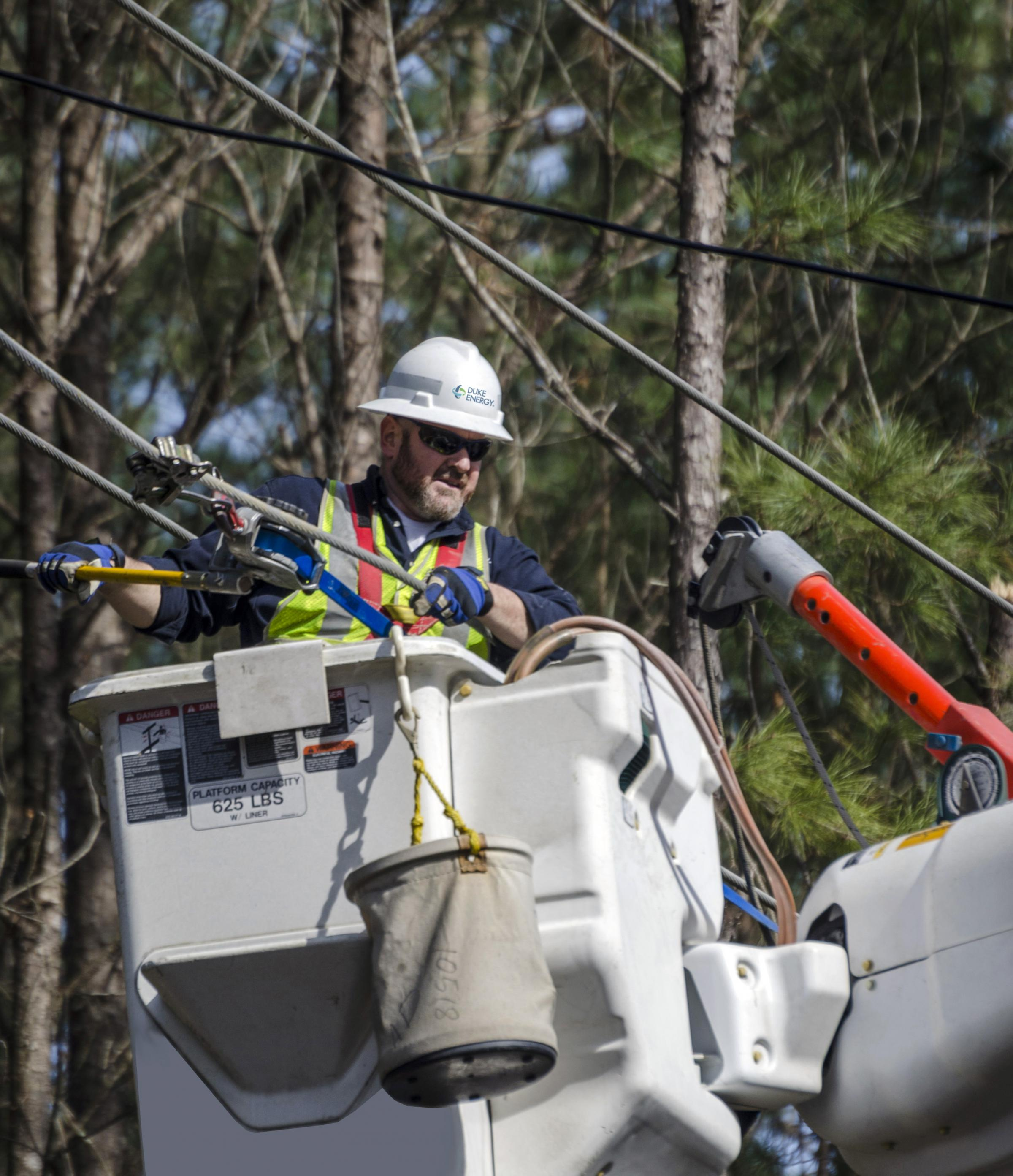 A Duke Energy worker restores power after a storm