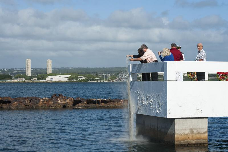 """Joanne Smith anJohnny W. Wallin scatter the ashes of their father, Pearl Harbor survivor John """"Spike"""" Wallin, at the USS Utah Memorial.  His ashes joined the remains of Sailors still aboard USS Utah, which was sunk during the 1941 attack."""