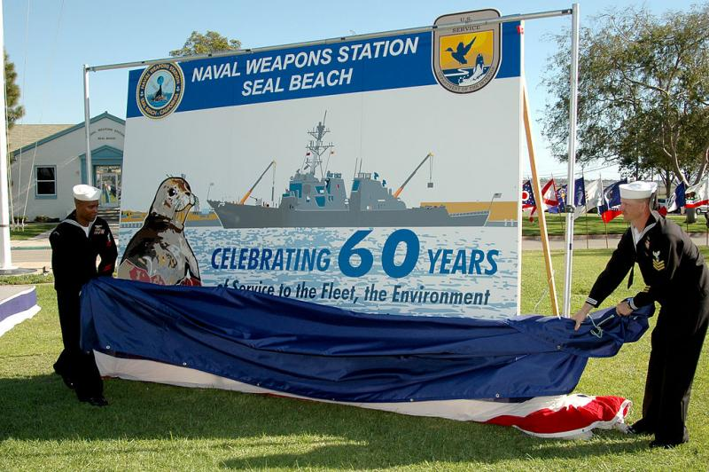 Christopher Yates(left) and  Jerry Tullos, unveil a new sign commemorating the Seal Beach weapons station's 60th anniversary in 2004.