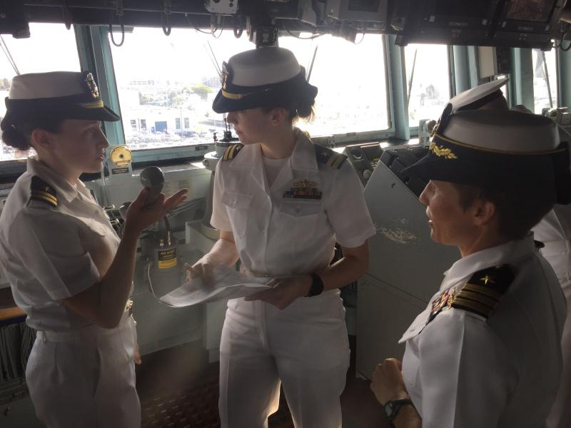 "Cdr. Mary Katey Hays (right) listens as the Officer of the Deck and the Junior Officer of the Deck run through the ""underway checklist"" on the USS Decatur."