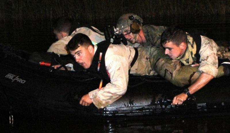 Marine Raiders navigate a Combat Rubber Raid Craft during a nighttime training exercise near Mobile, Alabama.
