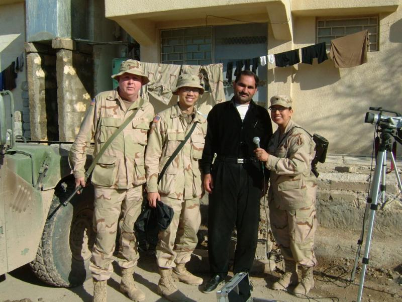 Bobby Yen, an Army Reservist serving in Iraq in 2003, with other members of his unit, and their Iraqi interpreter, wearing black.