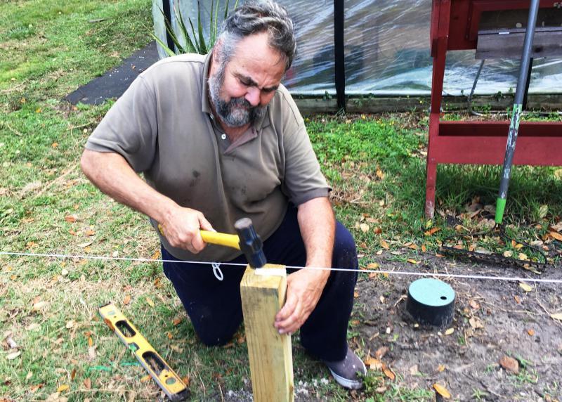 Marine Corps veteran Bernie Lodico straightens one of the fence posts in the Veterans Garden.