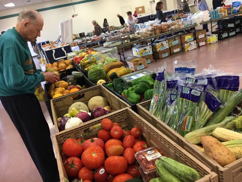 A volunteer with the Saddleback Church prepares produce as part of the group's food pantry on the Camp Pendleton Marine Base near San Diego. The church typically serves about 100 active duty military families as part of its monthly food pantry.