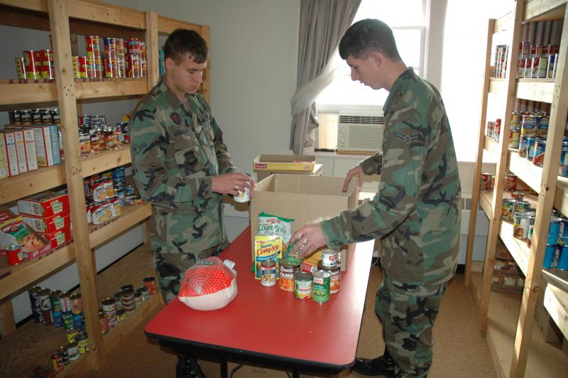 Airman Michael Hanselman and Benjamin Lee work in the Food Pantry at Minot Air Force Base in North Dakota. They're assembling baskets that will be distributed to needy military families.