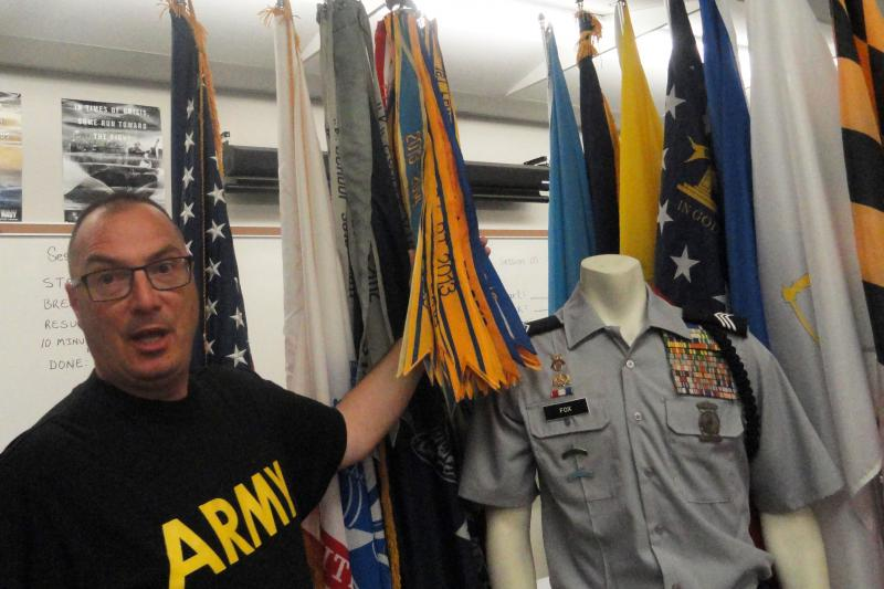 Retired Army Lt. Col. Mo Bolduc shows the display of ribbons and flags that adorn the JROTC room and computer lab at his Florida high school.