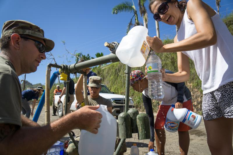 Sgt. Gary Wyckoff (left) helps residents fill containers with drinkable water in Utuado, Puerto Rico. Troops from Fort Bragg are using a filtration system to purify the water.