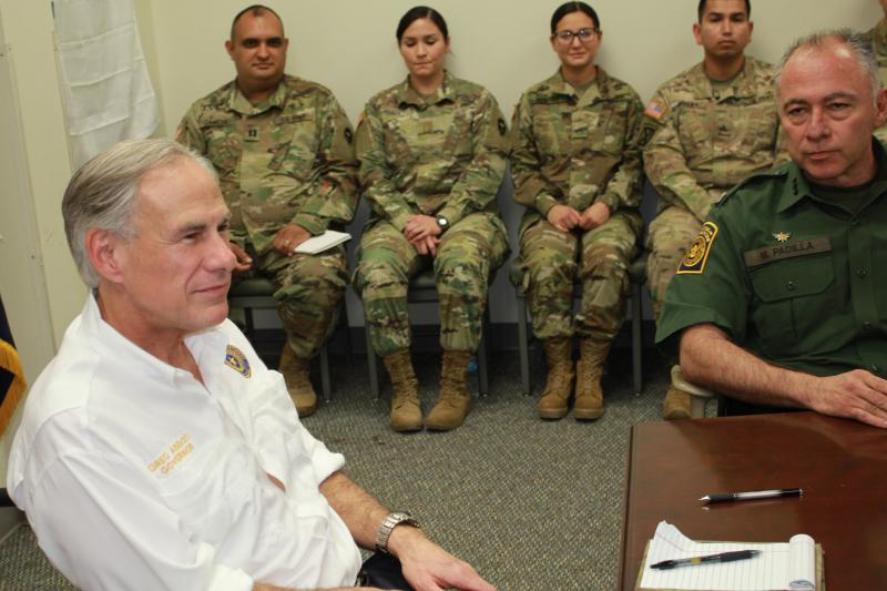 Texas Gov. Greg Abbott (left) and Manuel Padilla, chief of the Rio Grande Valley Border Patrol Sector, meet National Guard troops in Weslaco, Tex.