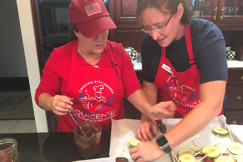 Chef Ellen Adams (right), an Air Force veteran, helps fellow veteran Linda Costello coat apples in chocolate.