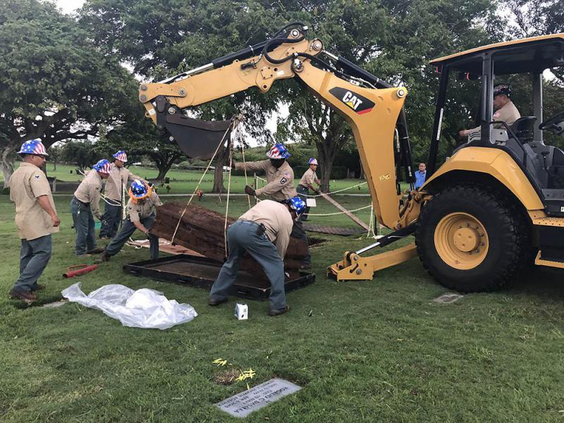 A VA cemetery crew lifts a steel casket from the ground containing remains of an unknown U.S. service member, more than six decades after it was buried.
