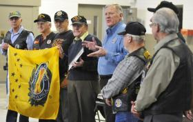 Barry Rice, center, presents the newest Chapter of the Vietnam Veterans of America, #1073 in Knoxville, their charter and VVA flag.