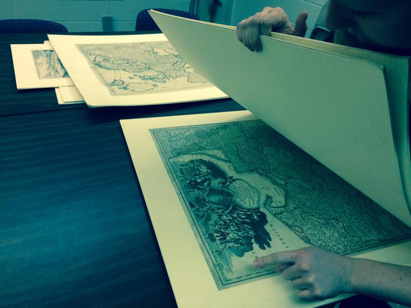 Lindsey Waugh leafs through several ancient maps recently entered into the McClung Museum collection