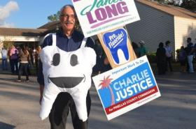 Pediatric dentist Johnny Johnson campaigns to replace Nancy Bostock and Neil Brickfield on the county commission because they voted to stop adding fluoride to water supplies.