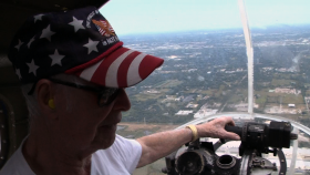 William Yepes, a World War II bombardier, sits in the nose of the B-17 bomber during its flight over Tampa Bay.