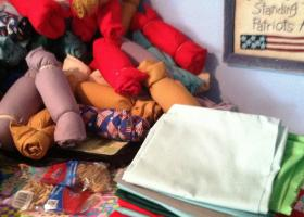 A pile of finished pillows rolled up and bound with rubber bands stands next to a stack of fabric casings waiting to be stuffed.