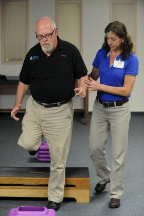 Physical Therapist Margie Moore works with Bruce Wright, a patient living with Parkinson's disease, as they demonstrate a walking and balance exercise. These and other physical therapy techniques are used to retrain the mind to do everyday things. Wright undergoes physical therapy at Florida Hospital Tampa's physical therapy facility.