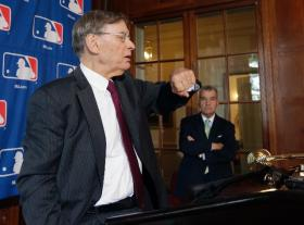 MLB Bud Selig checks his watch before a news conference following baseball meetings in Cooperstown, N.Y. Thursday. Atlanta Braves President John Schuerholz is at right.