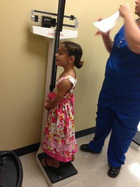 Catalina Hernandez, 7, gets weighed and measured at a free back-to-school health fair.