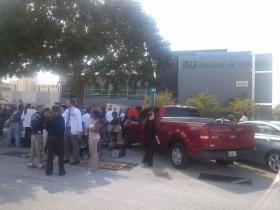 Employees stand outside the USF Nursing building after being evacuated for reports of a suspicious man.