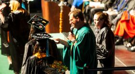 Honors College Dean Stuart Silverman reads one of the estimated 80,000 to 100,00 graduates' names at a USF commencement ceremony. He'll hang up his cap and gown this weekend after a quarter century serving as the graduation announcer.