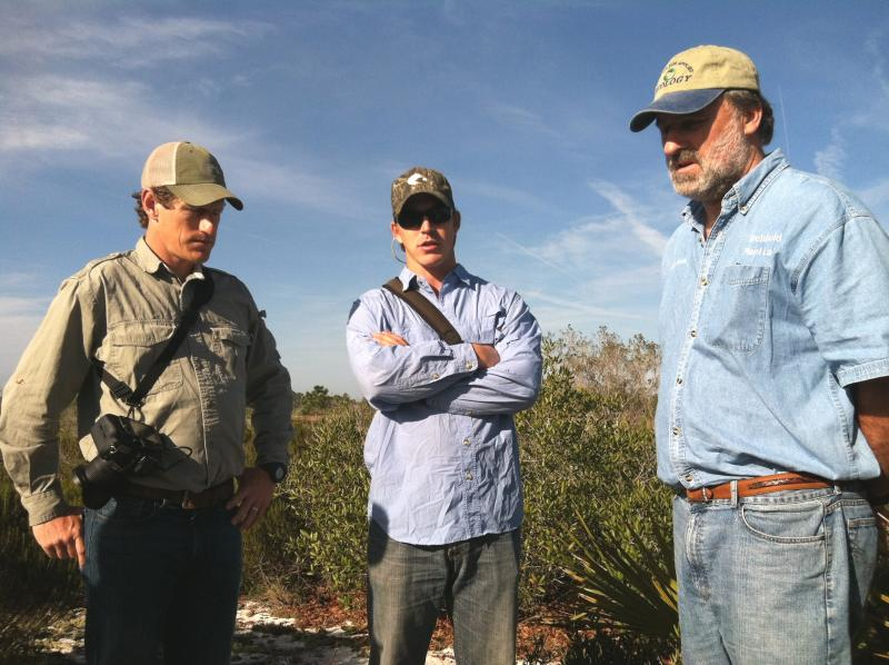 Expedition members Carlton Ward Jr., left, and Joe Guthrie get a tour of the scrub from Archbold plant ecologist Eric Menges