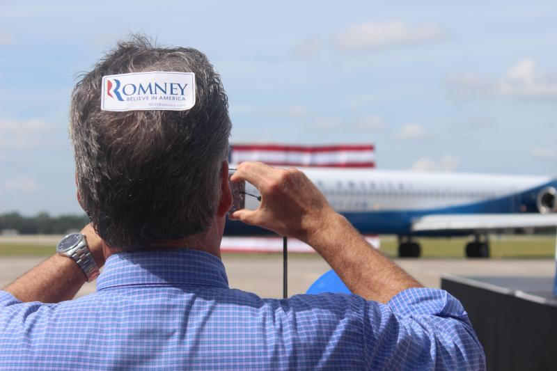 A Romney supporter takes a picture as the new campaign aircraft prepares for takeoff.