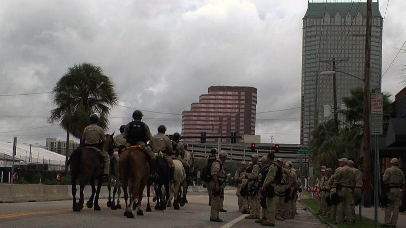 Tampa Police Department officers on horseback pass by a group of police on foot on a roadblocked downtown Tampa street.