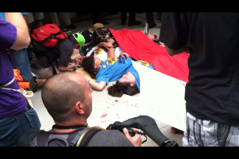 For a short period of time, about a half dozen demonstrators lay down on the sidewalk in front of the theater. A long piece of red fabric was spread over their torsos.