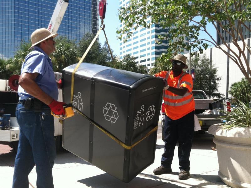 Workers return trash cans that were removed from the Franklin Street Mall for the convention