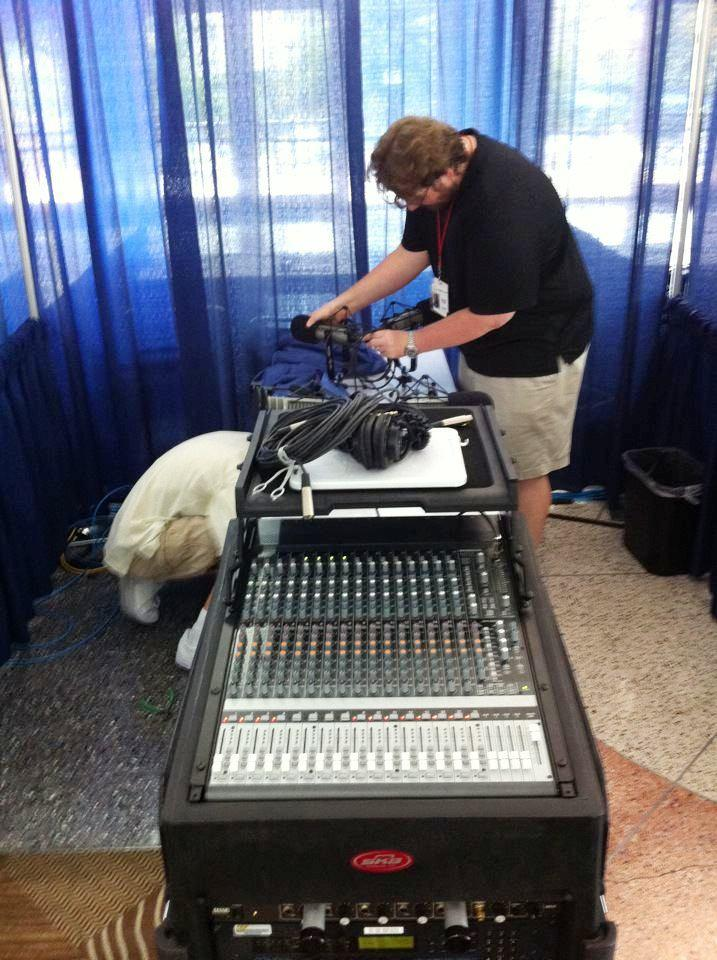 Engineers Mike O'Shea (left, under table) and Dustin Hapli set up Florida Matters: The Convention in the Tampa Convention Center