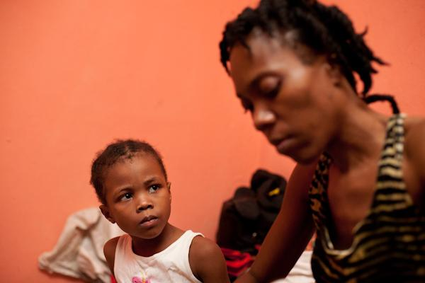 Fabienne's daughter, Christina, looks intently at her mother as she dresses her.