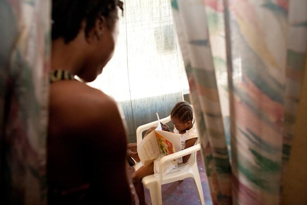 Fabienne looks toward her daughter, Christina, as she looks at a book.