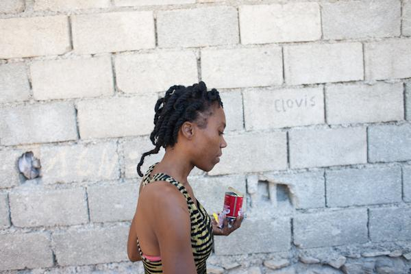 Fabienne walks alongside an exterior wall of her home after purchasing some ingredients from her neighbor.
