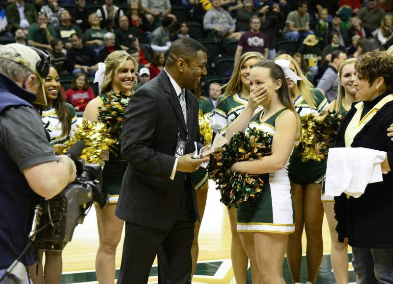 USF College of Pharmacy Dean Kevin Sneed, hands USF cheerleader Ellen Bickel her letter of acceptance