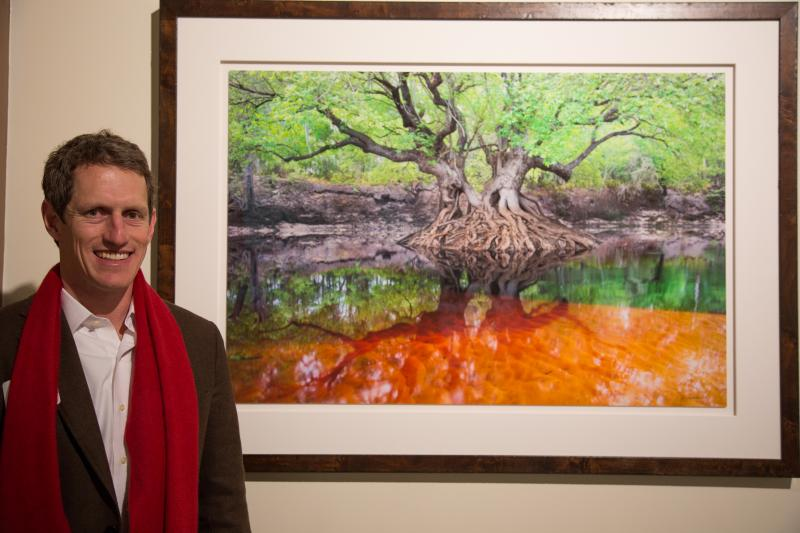 Carlton Ward, Jr. next to a photograph of a tree along the Suwannee River, in the Tampa Bay History Center