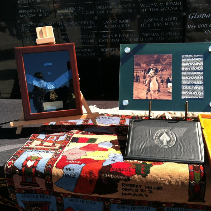 A tribute to Staff Sergeant Miller - the Congressional Medal of Honor, a plaque with a photo of him on a horse in Afghanistan and a rug given to his family by the Afghan soldiers whose lives Miller saved.