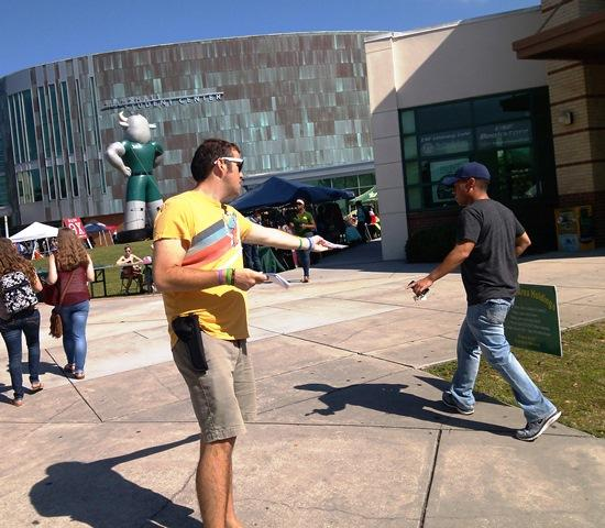 Junior Tommy Rayder, technology director for USF College Republicans, hands out flyers at USF Bull Market