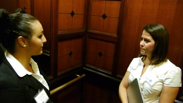 "USF College of Business Student (left) conducts an ""elevator interview"" with a judge"