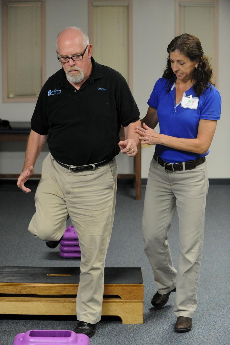 :Physical Therapist Margie Moore works with Bruce Wright, a patient living with Parkinson's disease, as they demonstrate a walking and balance exercise. These and other physical therapy techniques are used to retrain the mind to do everyday things.