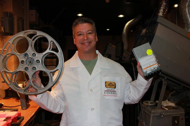 Projectionist Gary Dowling compares a 33-millimeter reel, which holds 20 minutes of film, with a digital format that contains an entire movie.