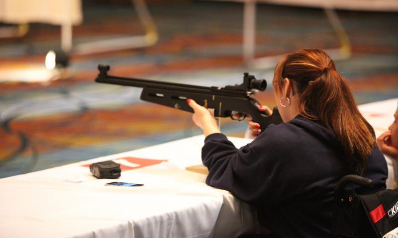 A Veteran fires an air rifle at the 32nd National Veterans Wheelchair Games.