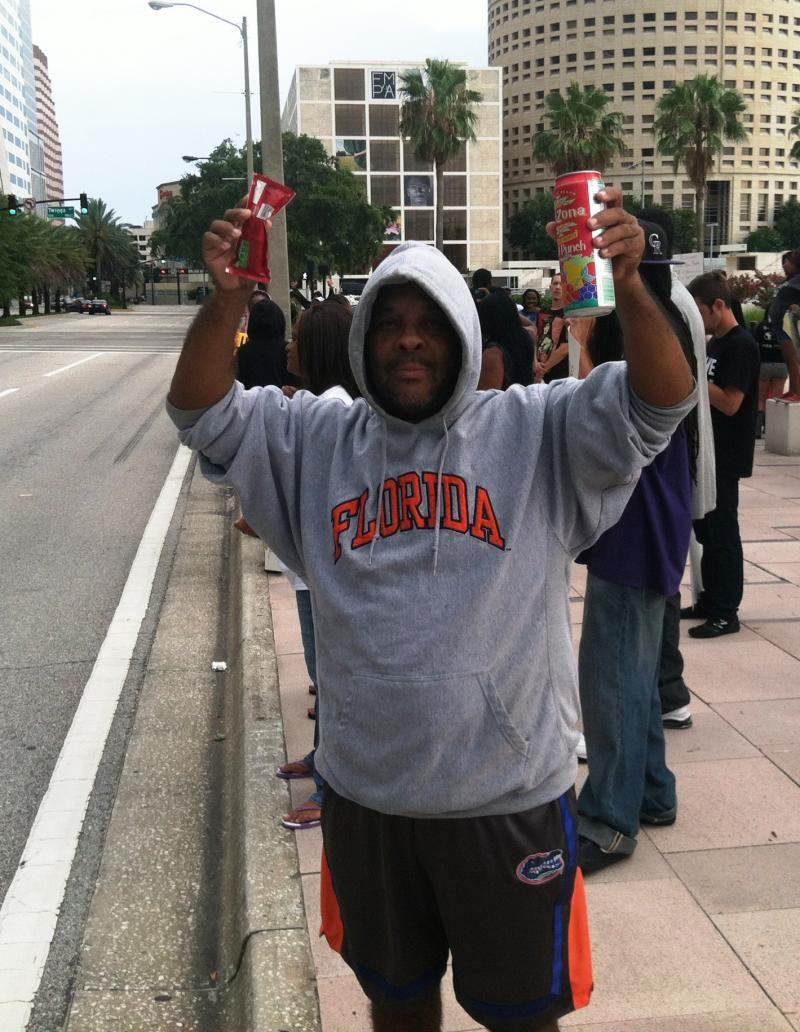A protestor mimics Martin, holding Skittles and an iced tea