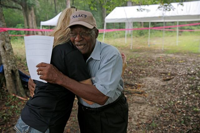 Erin Kimmerle hugs Elmore Bryant, a former Dozier School employee and a former mayor of Marianna, on the site of the Boot Hill cemetery Saturday.