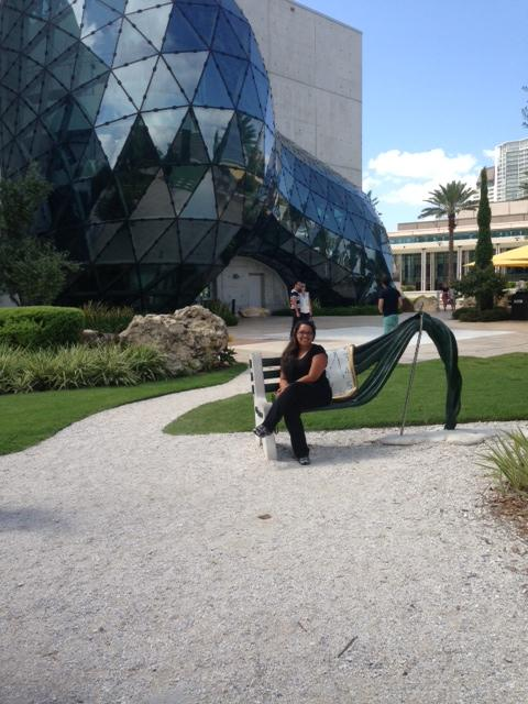 WUSF's Yoselis Ramos sits on a melting bench in front of the Dalí Museum's enigma.